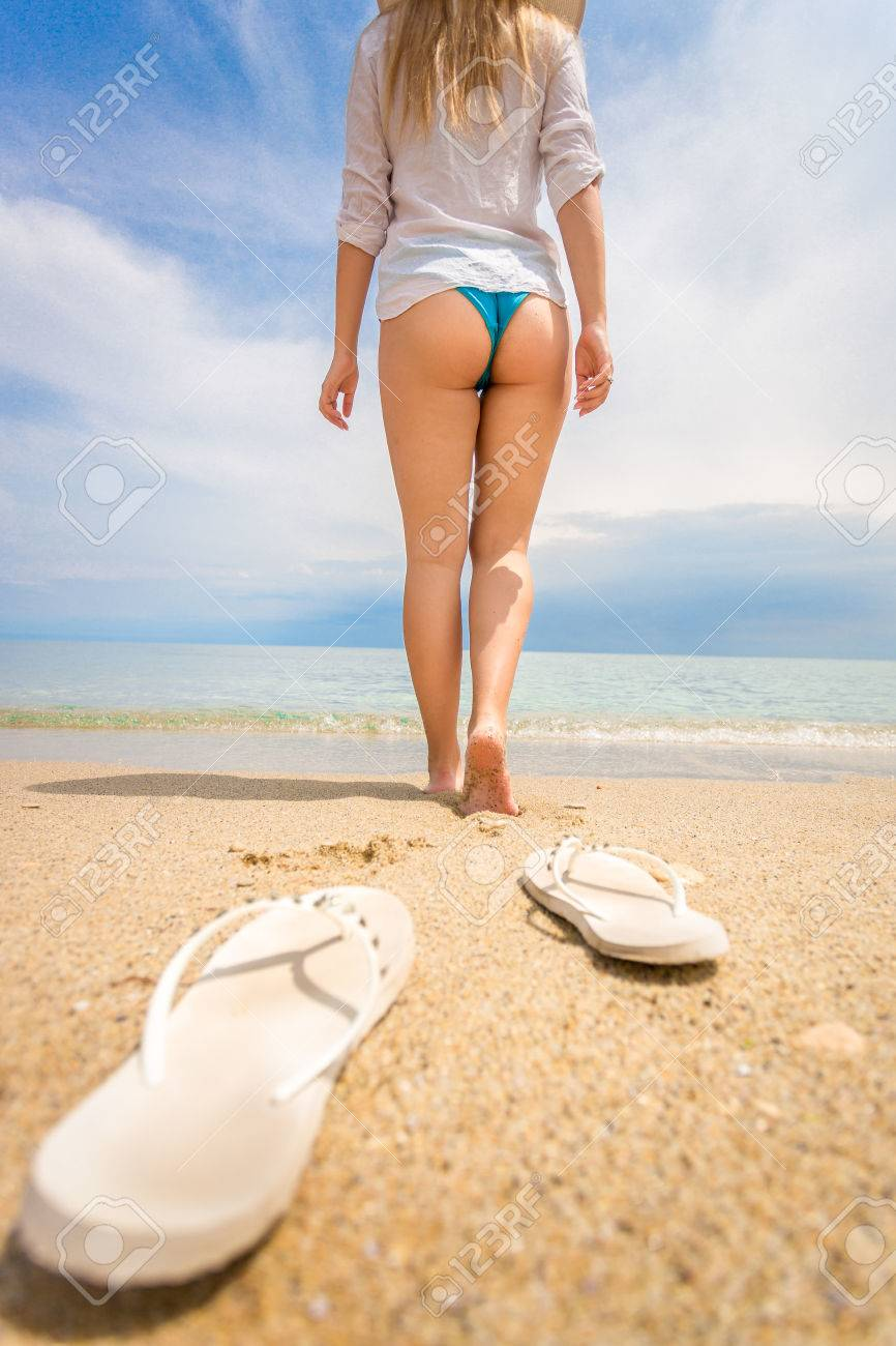 dd9e4f30a92c Closeup shot of young woman taking off flip flops and and walking on the beach  Stock