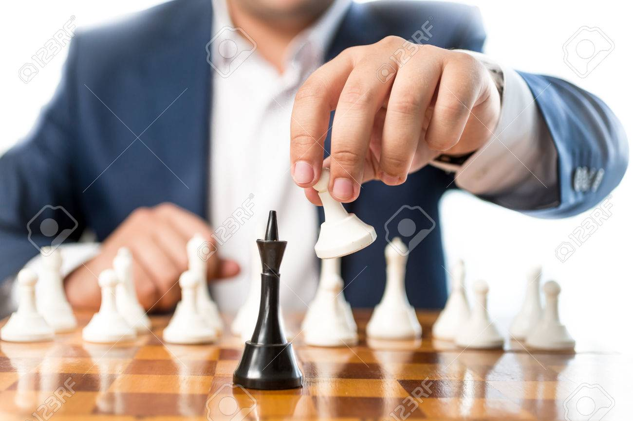 Closeup photo of businessman playing chess and beating black king - 41474459