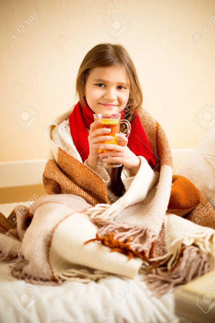 portrait of cute girl covered in blanket drinking hot tea with