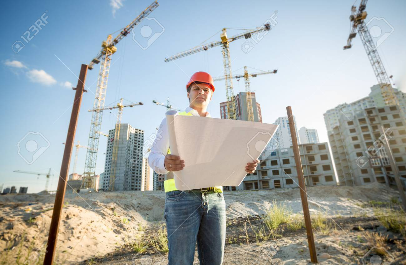 Construction engineer in hardhat inspecting blueprints on building site - 41681533