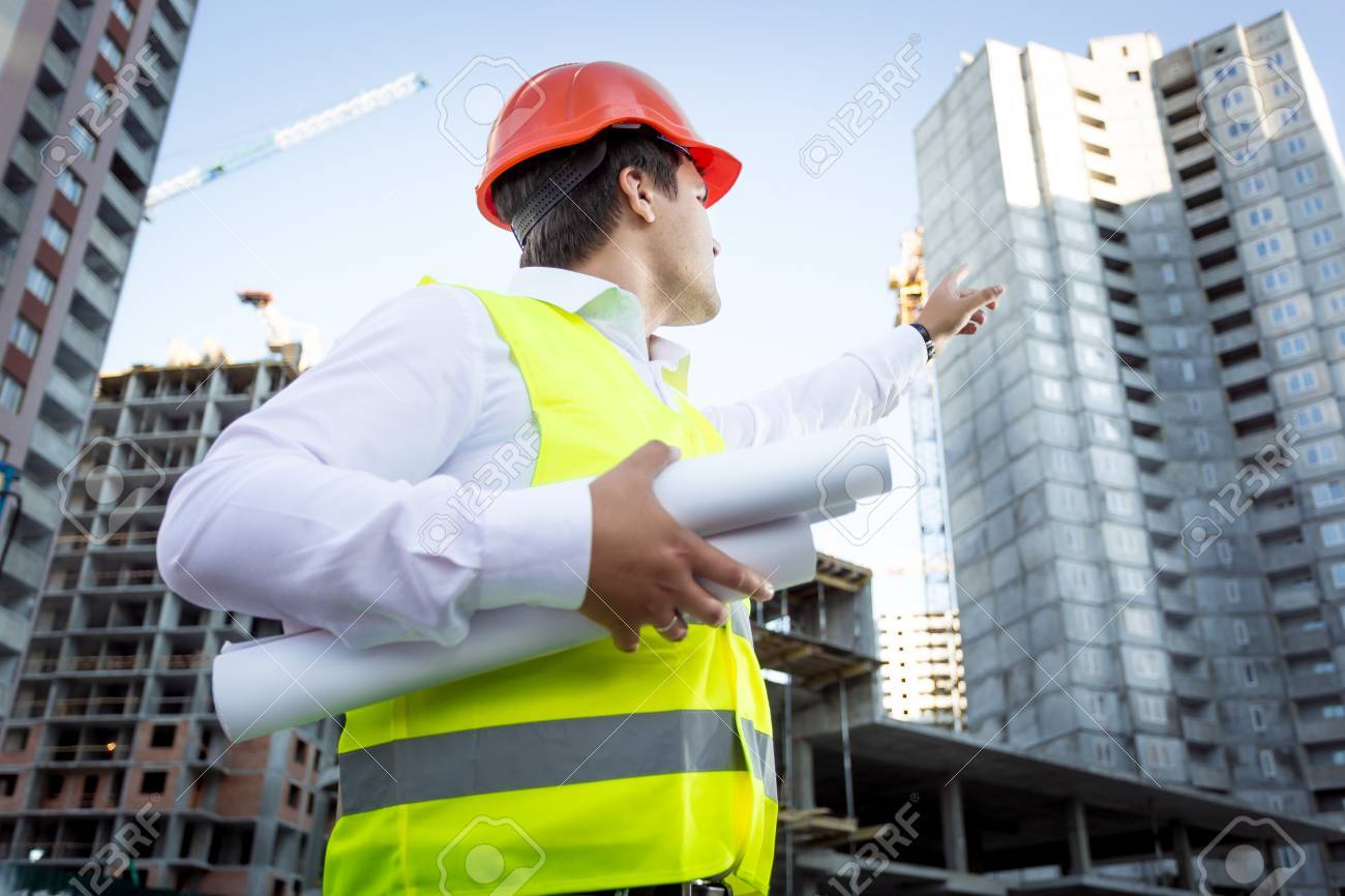 Closeup portrait of foreman with blueprints pointing hand at high building - 41681545