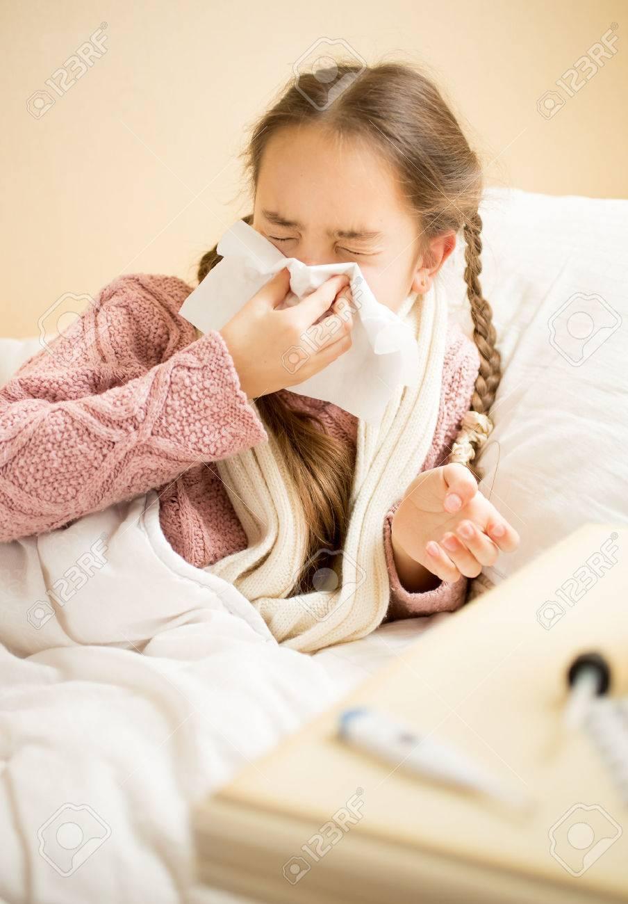 Portrait of cute little girl blowing nose in paper handkerchief - 41681573