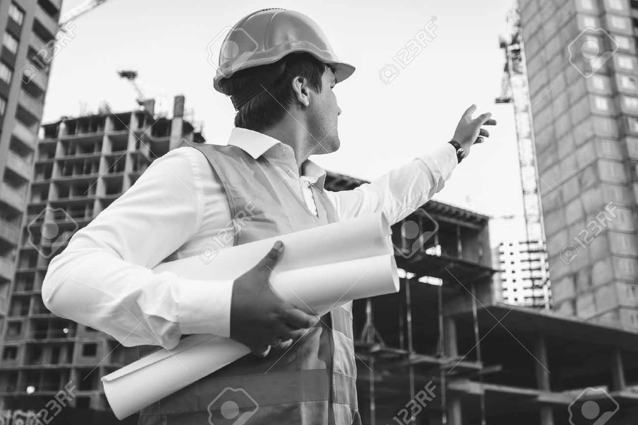 Black and white closeup photo of engineer with blueprints checking building site construction - 41681593