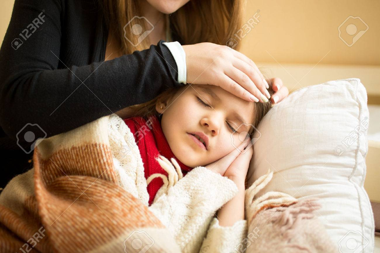 Closeup photo of caring mother holding head on sick daughter forehead - 41681672