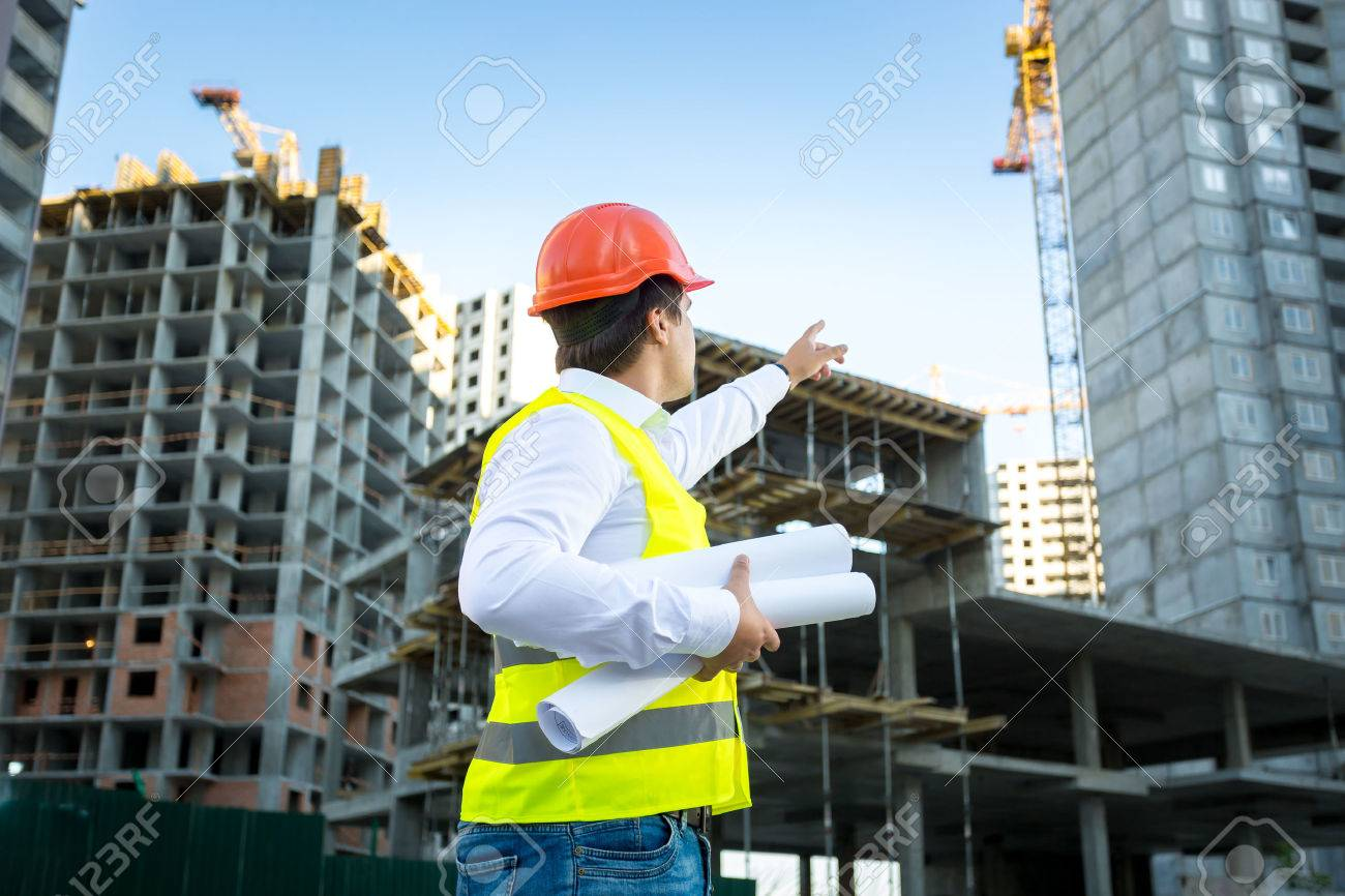 Site manager in hardhat pointing at crane on building site - 41681675