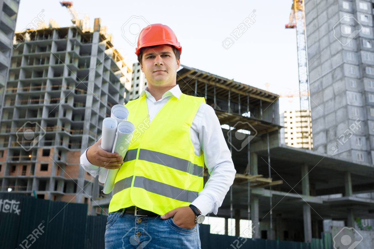 Portrait of site manager posing with blueprints against unfinished building - 41681721