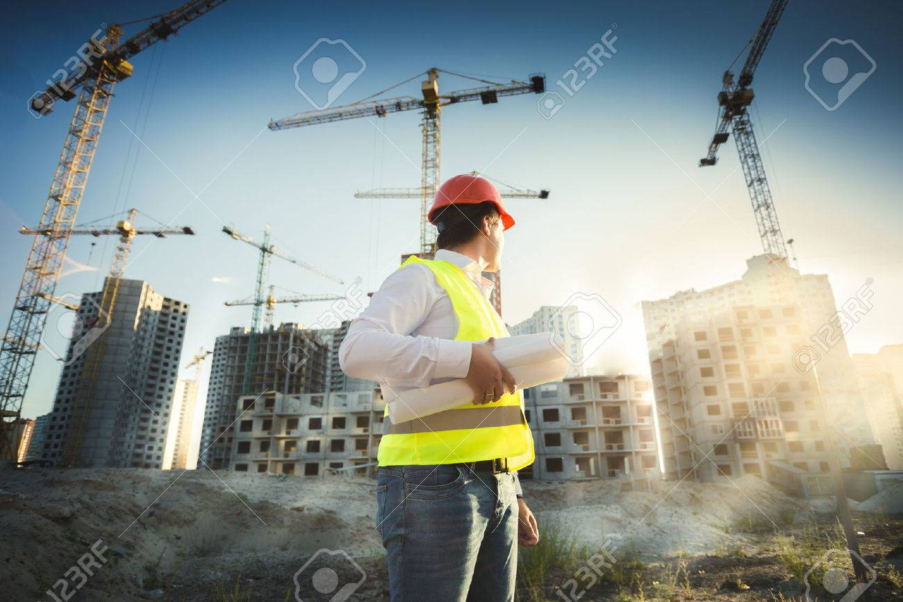 Man in hardhat and green jacket posing on building site at sunset - 41681756