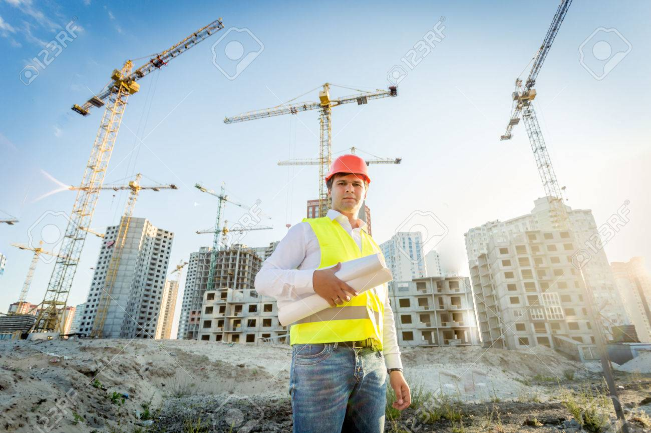Portrait of construction inspector posing with blueprints on building site - 41681874
