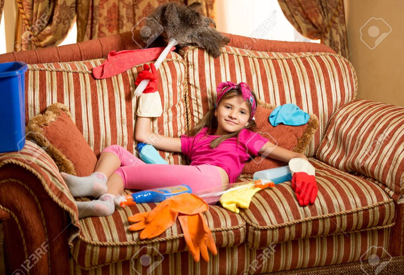 Funny photo of exhausted girl relaxing on sofa after cleaning