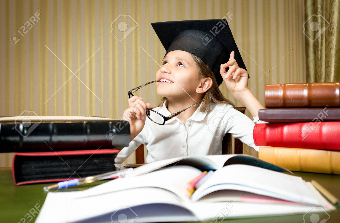Portrait of smart thoughtful girl posing at desk in graduation cap - 43406719