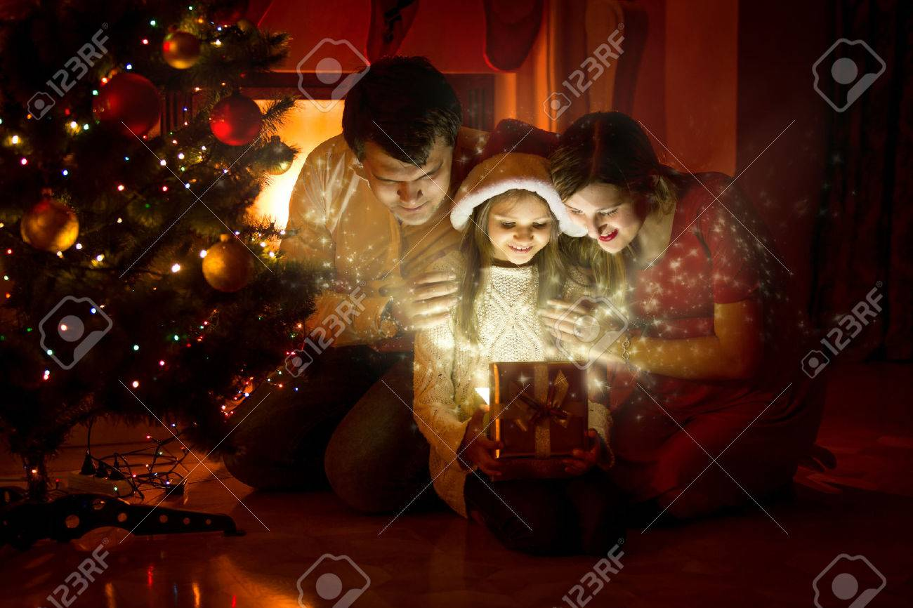 Happy family looking inside of magic Christmas gift box - 45161242
