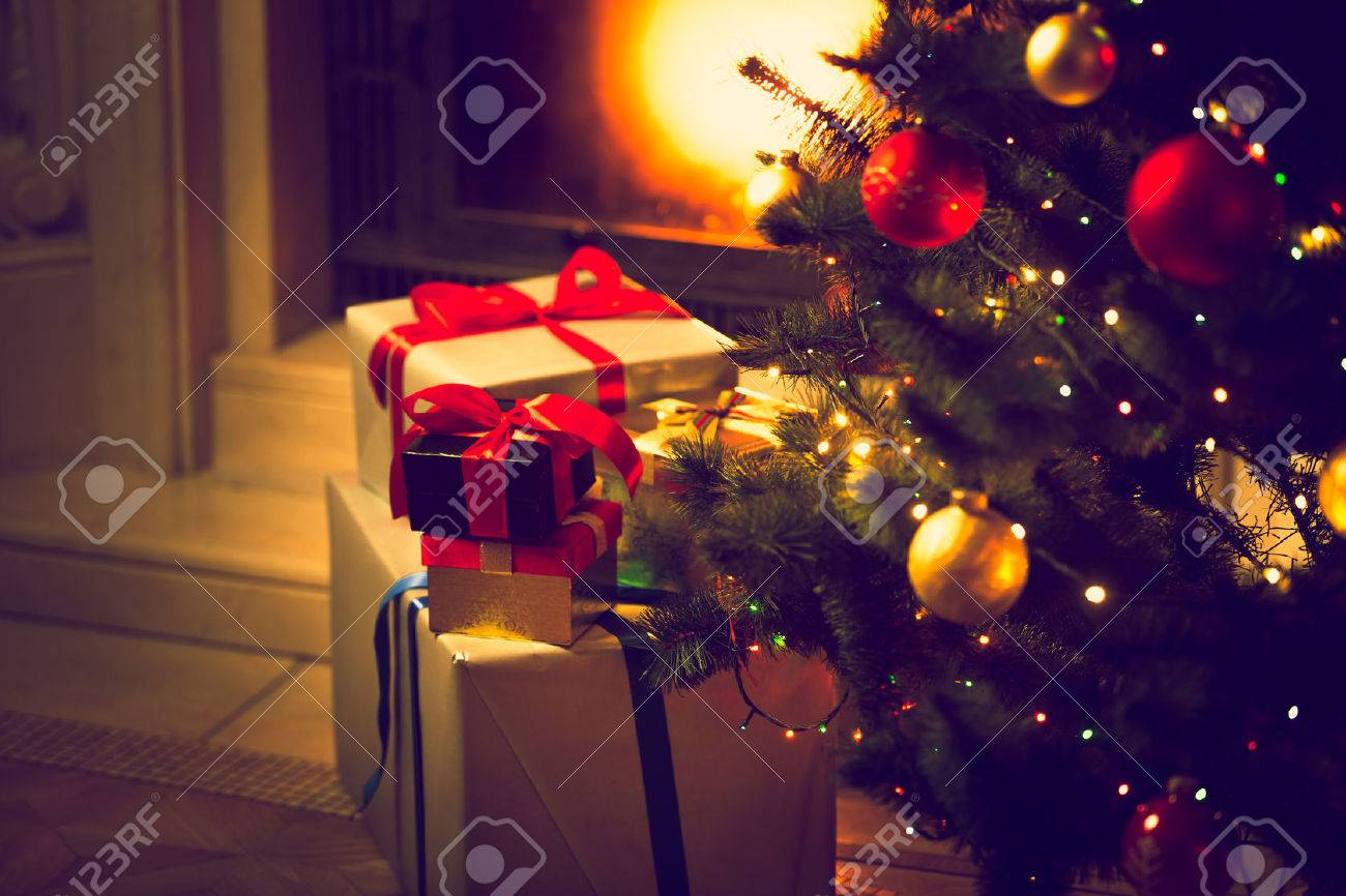Toned photo of decorated Christmas tree and gift boxes against burning fireplace - 45224436