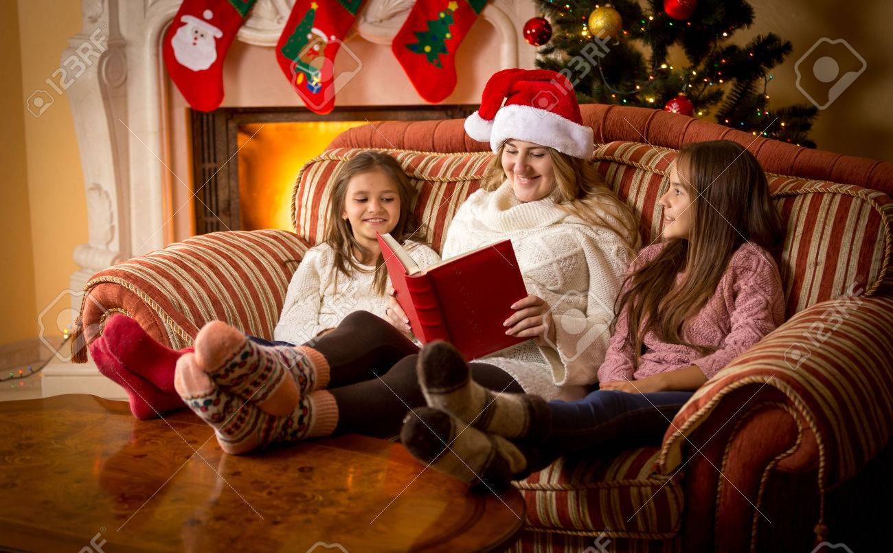 Happy woman reading book to daughters on sofa at fireplace at Christmas - 45161404