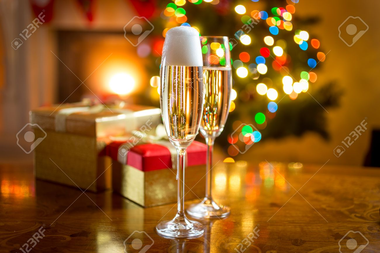 Two champagne glasses on table against fireplace decorated for Christmas - 45224695