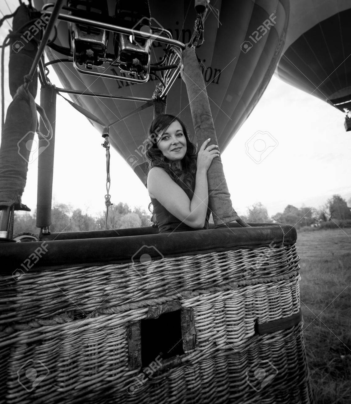 Black and white portrait of beautiful sexy woman posing at hot air balloon basket stock photo