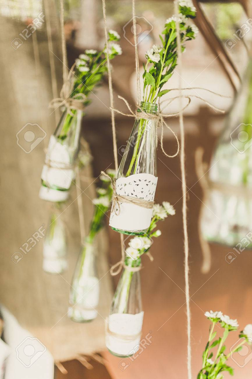 Closeup toned photo of decorated bottles with flowers hanging on twine - 46546378