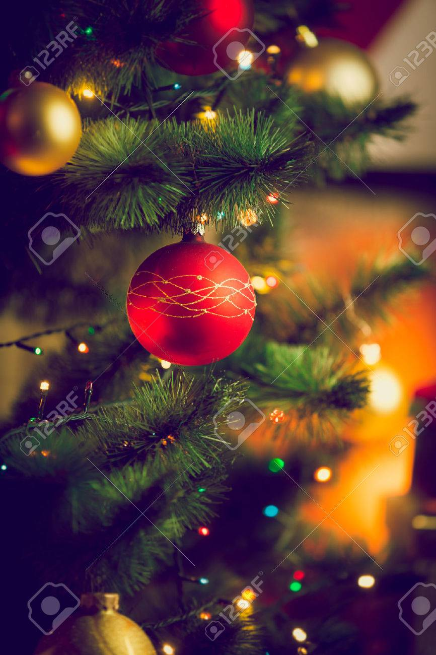 Closeup toned photo of red bauble on Christmas tree next to fireplace at living room - 46546505