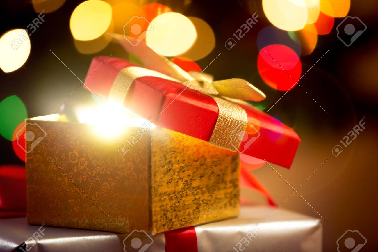closeup photo of open christmas gift box on glowing lights background stock photo 46546517