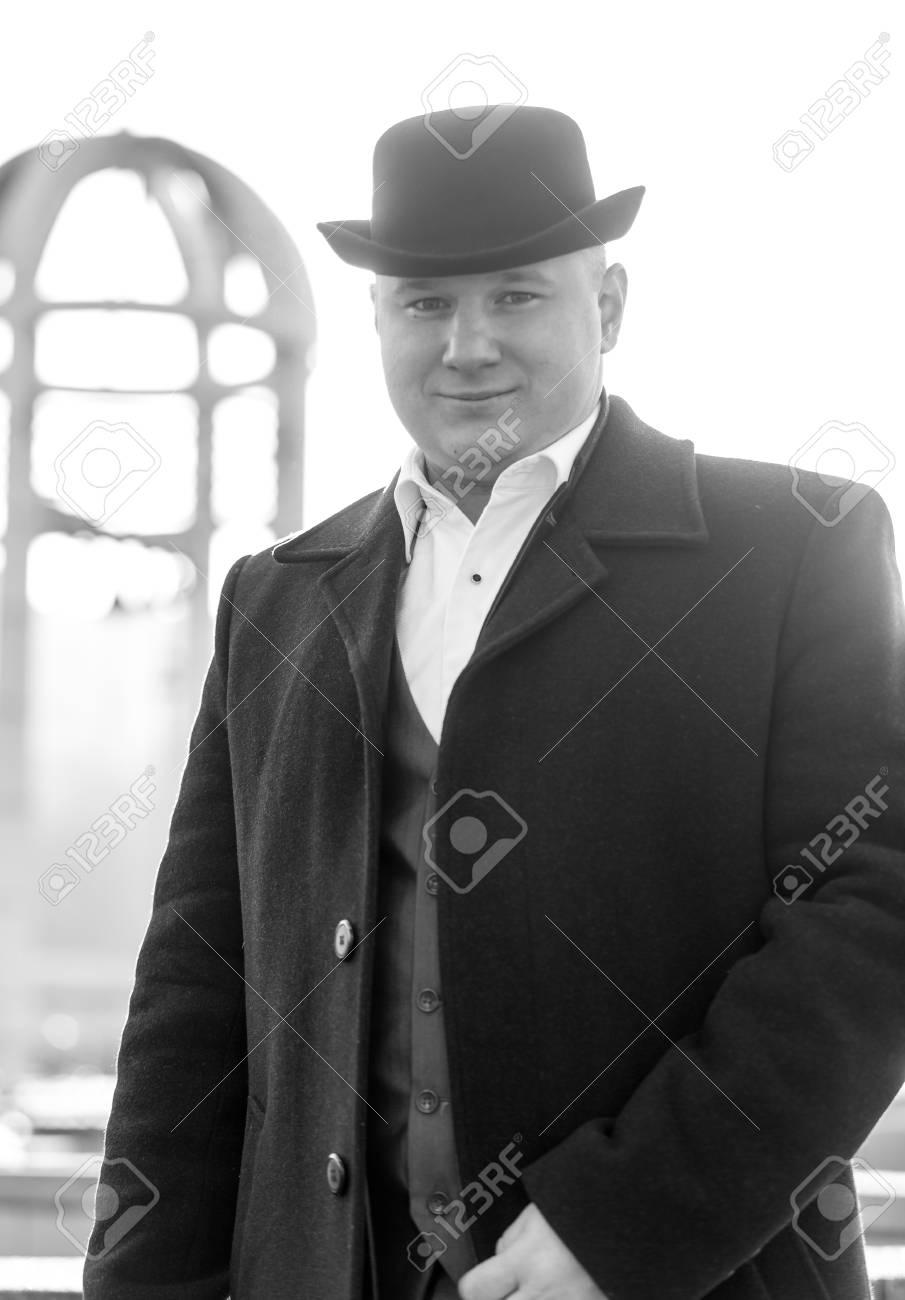 Foto de archivo - Retrato en blanco y negro de caballero joven sonriente en  el sombrero de bombín y chaqueta fc908278226