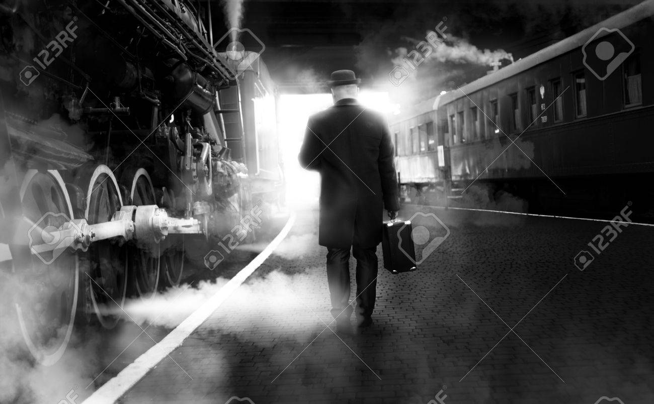 Black and white photo of man in vintage clothes walking on old railway station - 51875002