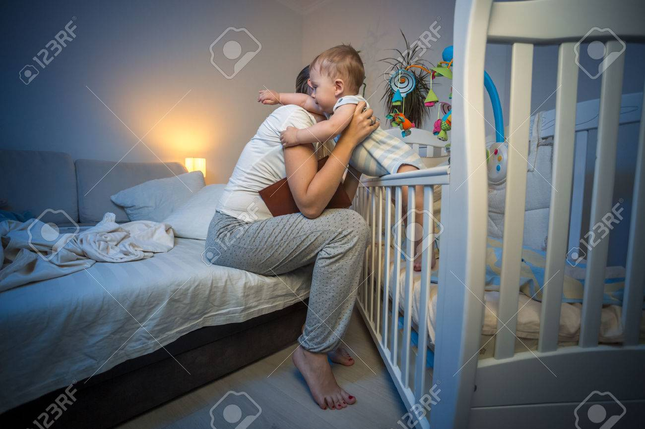 Cute baby boy got scared at night at hugging young caring mother - 62245248