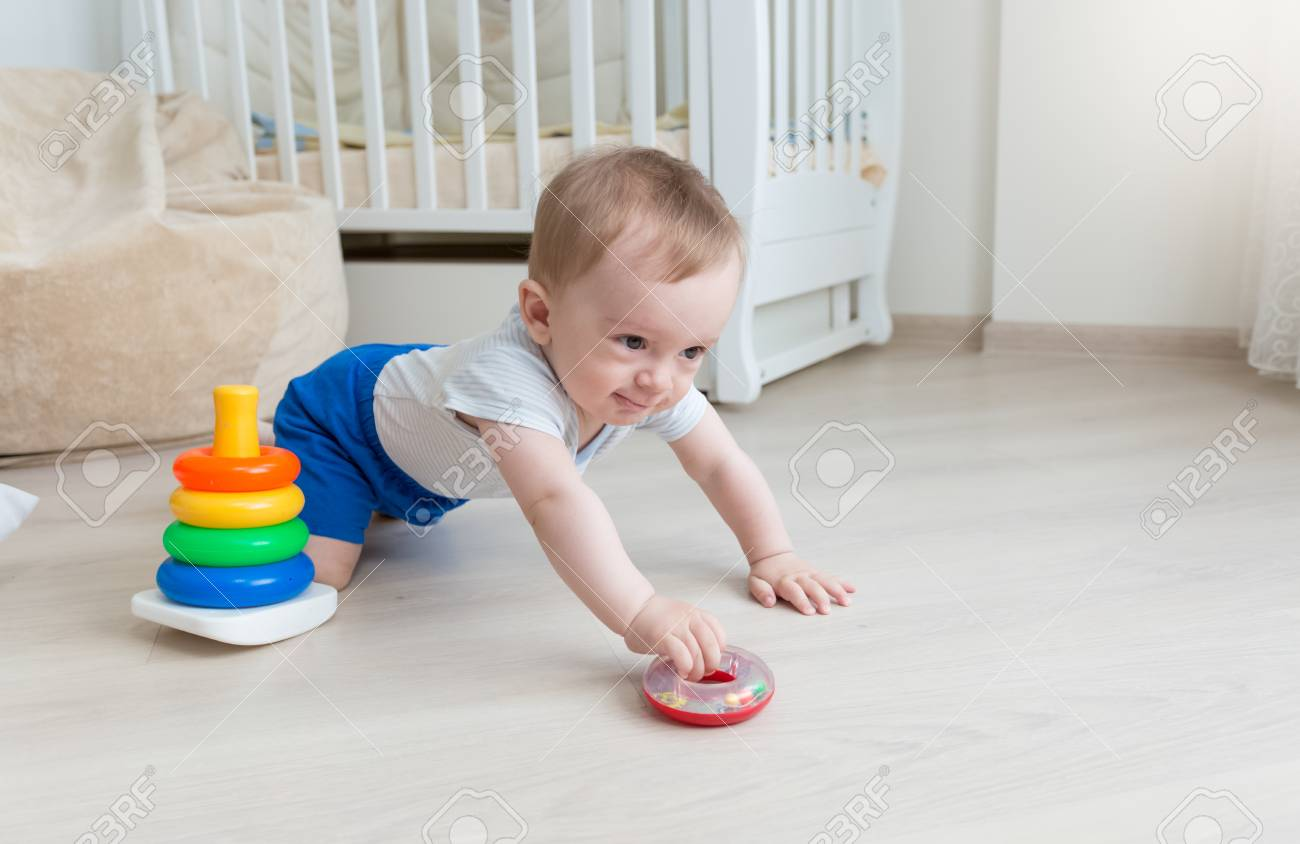 Adorable 9 months old baby boy playing with toy tower at living room stock photo