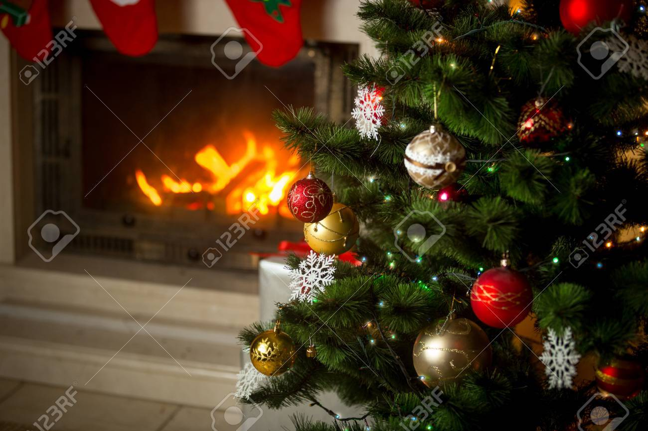 Burning Christmas Tree.Beautiful Decorated Christmas Tree In Front Of Burning Fireplace