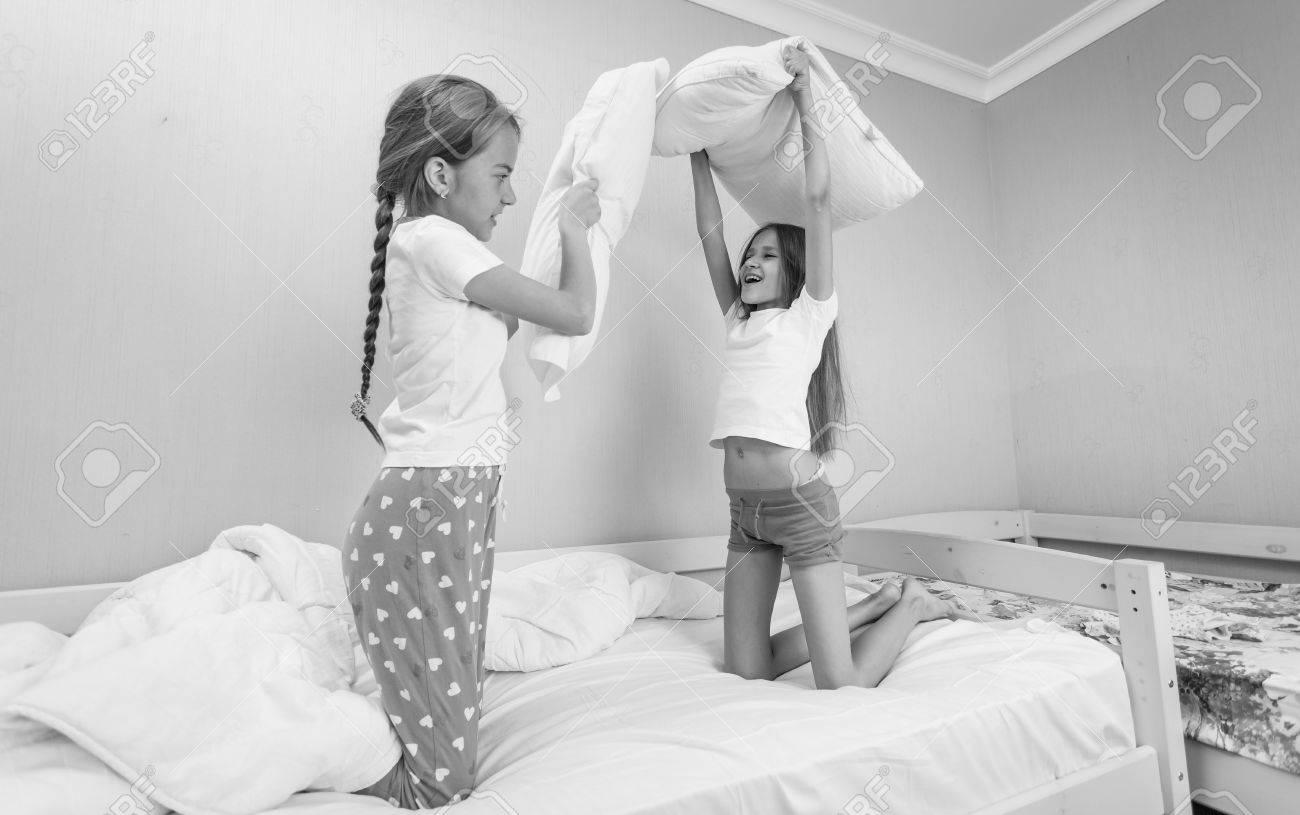 47142d3a96 Foto de archivo - Foto en blanco y negro de dos niñas con almohada luchar  en la fiesta de pijamas