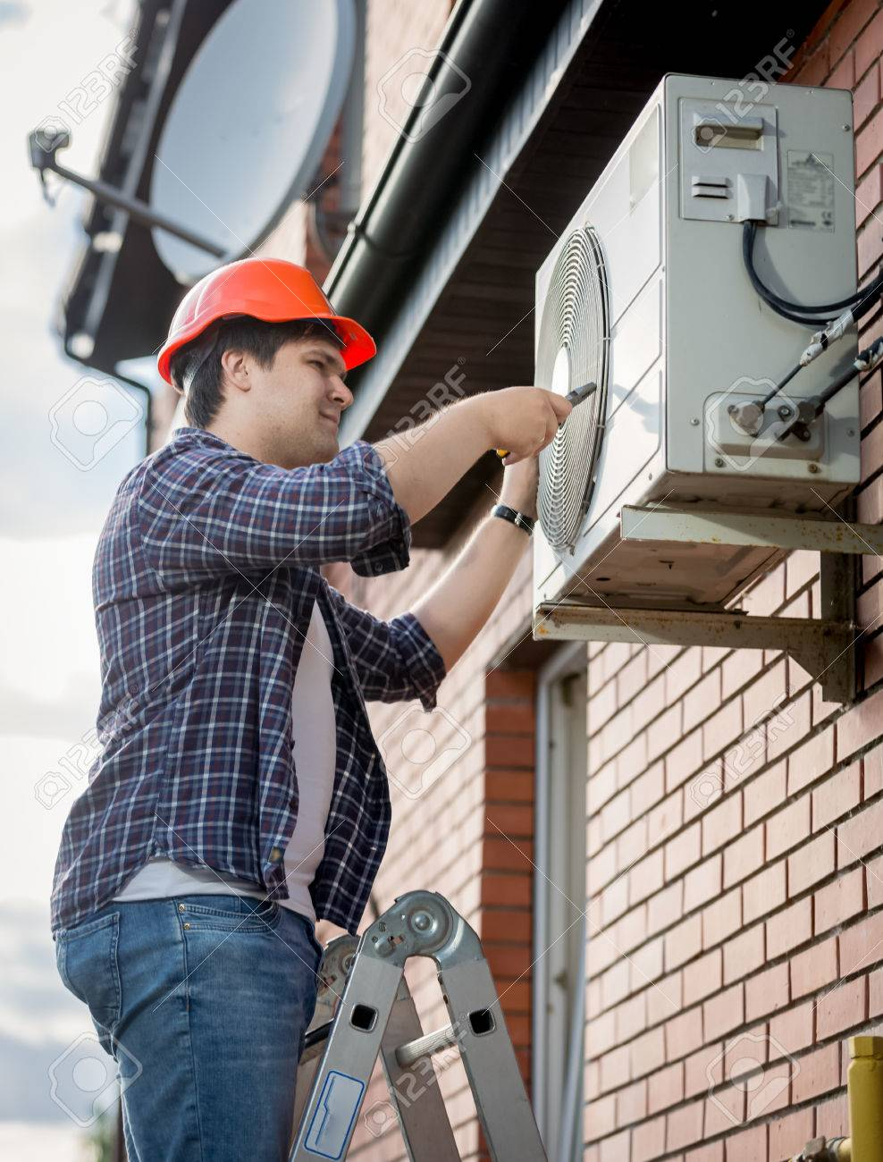 Young male technician repairing outdoor air conditioning system - 62493845