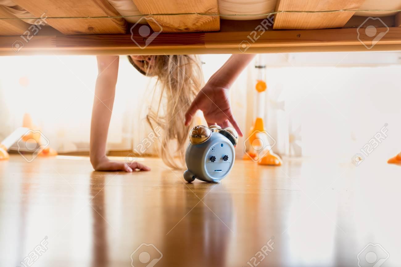 2d8df7ae6 Tonificado foto de la chica molesto para alcanzar despertador debajo de la  cama en la mañana