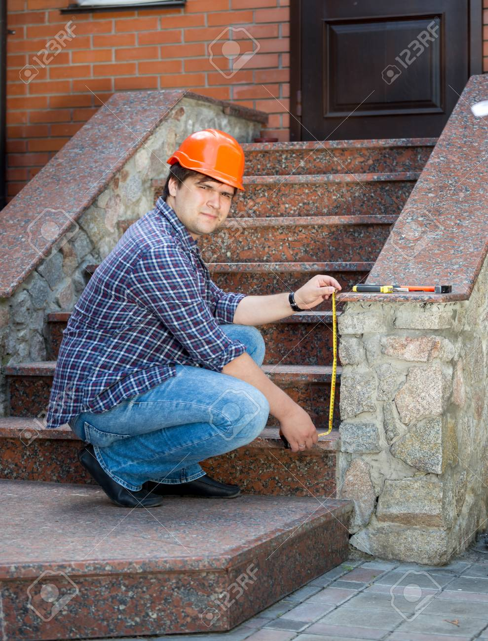 Stock Photo   Young Contractor Worker Measuring Stone Staircase With  Measuring Tape
