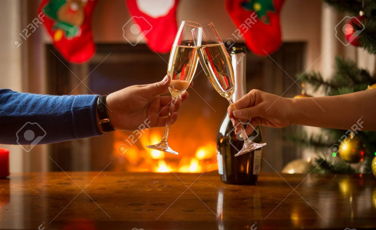 Closeup of man and woman celebrating Christmas and clinking glasses with champagne at fireplace - 65303364