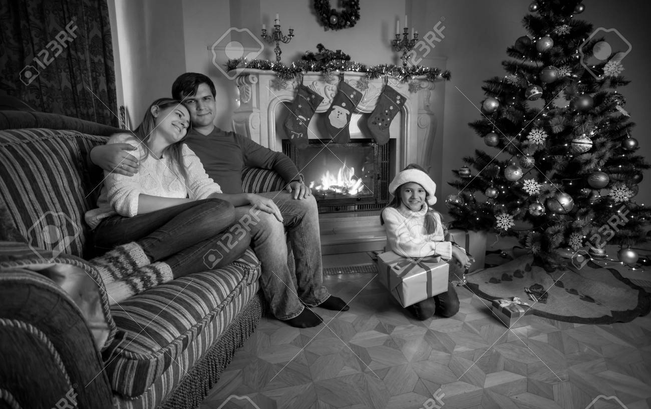 Black And White Image Of Happy Young Family Relaxing Near Fireplace