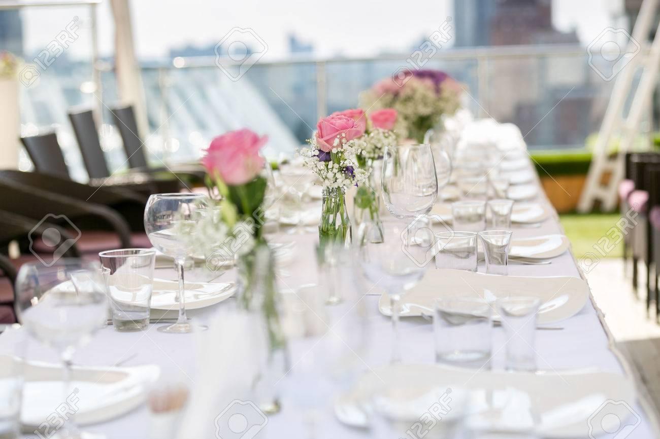Fila De Jarrones Con Flores En La Mesa Larga Sirvió Para El Banquete De Boda En Restaurante De La Terraza De Verano