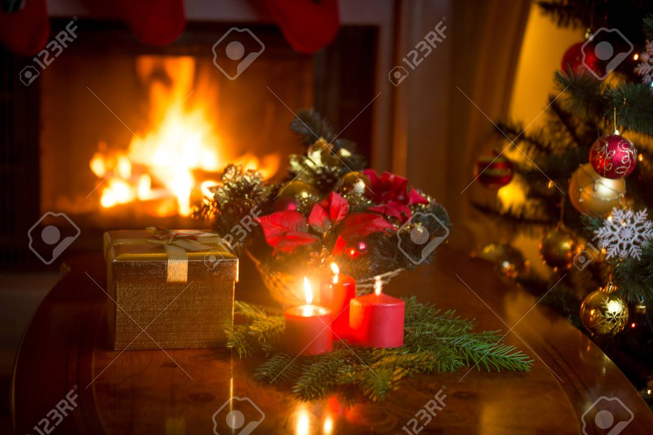Burning Christmas Tree.Burning Christmas Tree By The Fireplace And Golden Gift Box