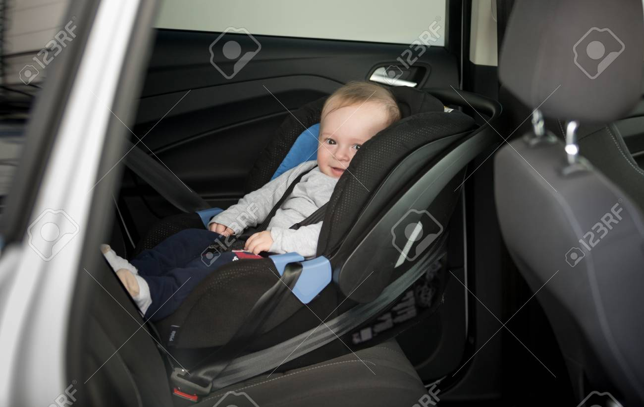 6 Months Old Baby Boy Sitting In Child Seat At Car Stock Photo