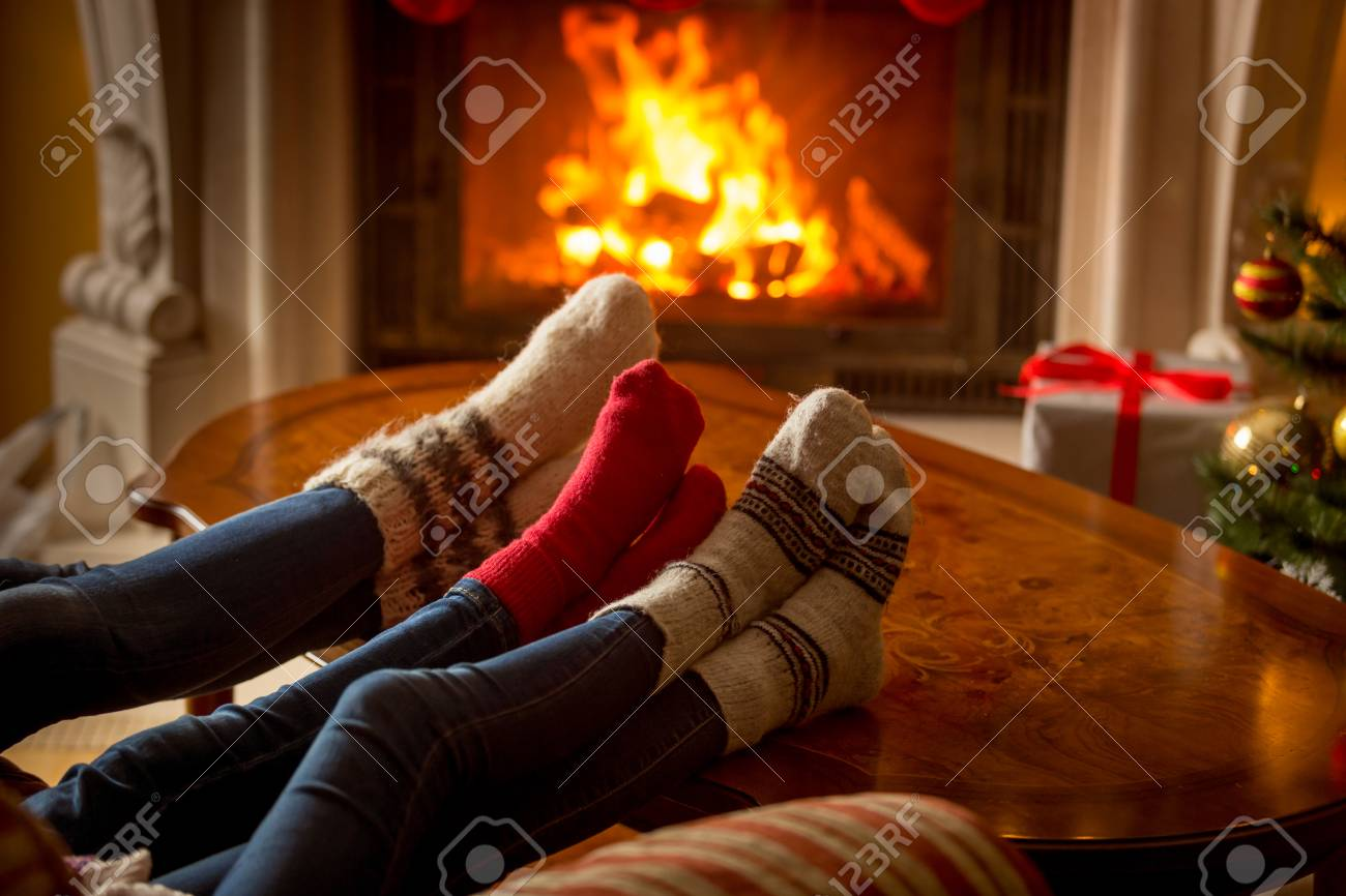 Male and female feet in woolen socks warming at burning fireplace - 81283285