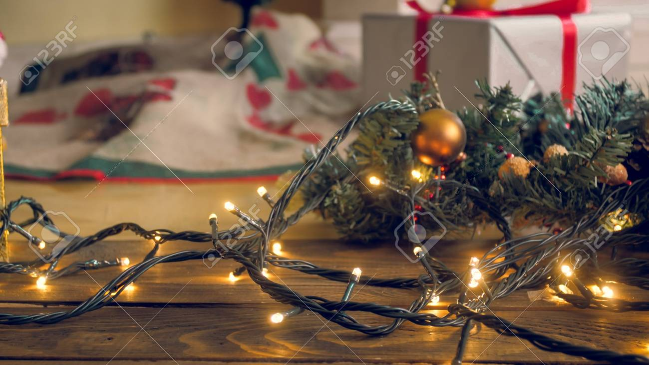 Closeup Toned Image Of Glowing Christmas Light On Wooden Floor At Living Room Stock Photo