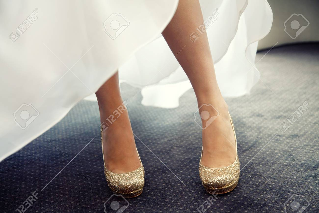 b7ee39a4e1c1 A beautiful bride in a white wedding dress stands outdoors with her pretty  gold wedding shoes