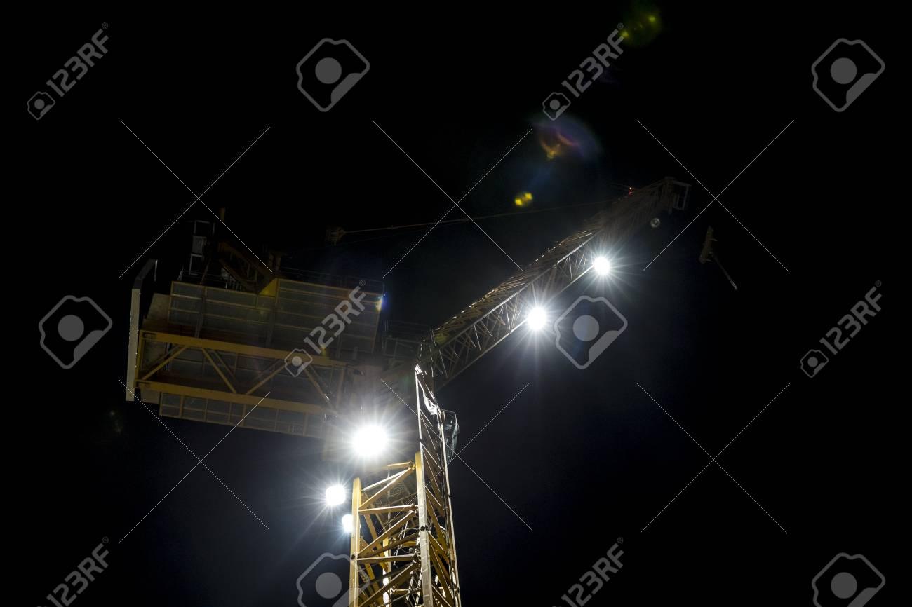 夜のライトアップ スポット ライト フレア コピー スペースを作成する低角度から建物建設用クレーン