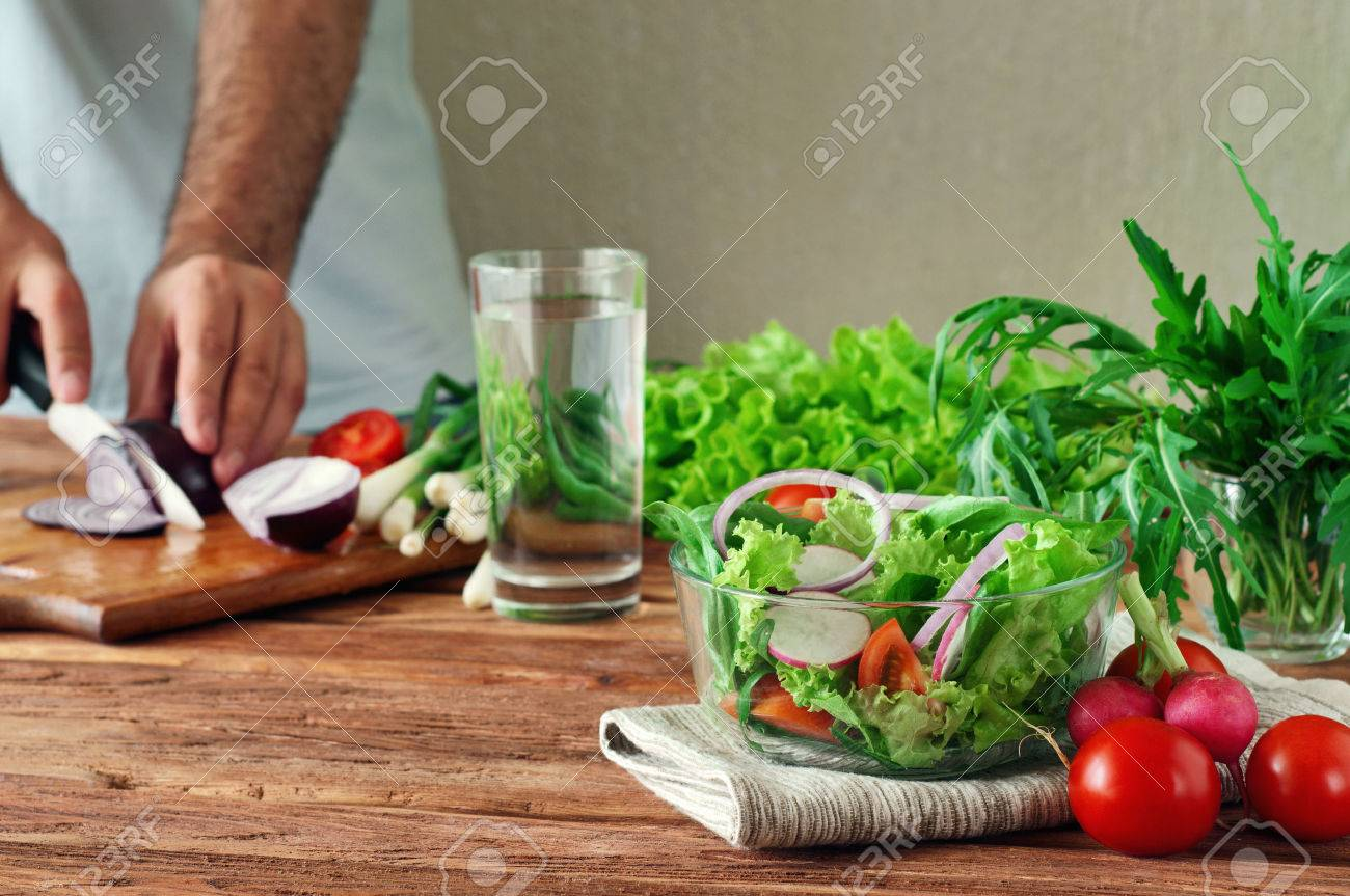 Fresh salad of summer vegetables in a deep bowl of glass. Arugula, lettuce, radishes, onions, cherry tomatoes. In the background male hand sliced onions on cutting board. - 50506189