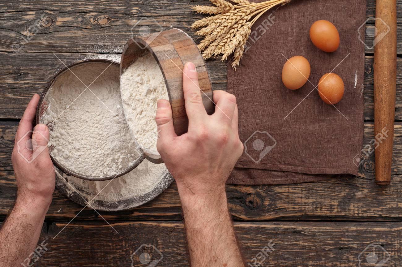bäcker das mehl sieben, brot auf einem holz dunkle oberfläche
