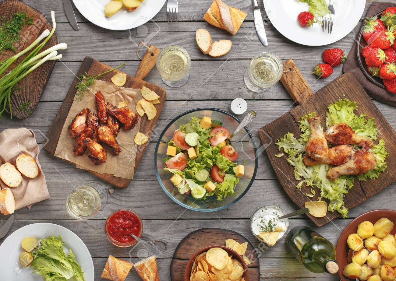 Different food cooked on the grill on a wooden table, grilled chicken legs, buffalo wings, salad, potatoes, bottle of wine and three glasses of wine and strawberry. - 60233284