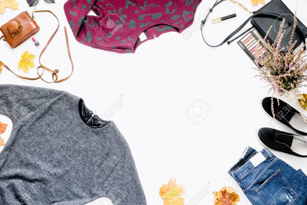 ... automne femme sur fond blanc. Cadre de robe, jeans, baskets, sac à  cosmétiques, appareil photo vintage et feuilles d automne. Concept de blog  de beauté. c89dd86581fd