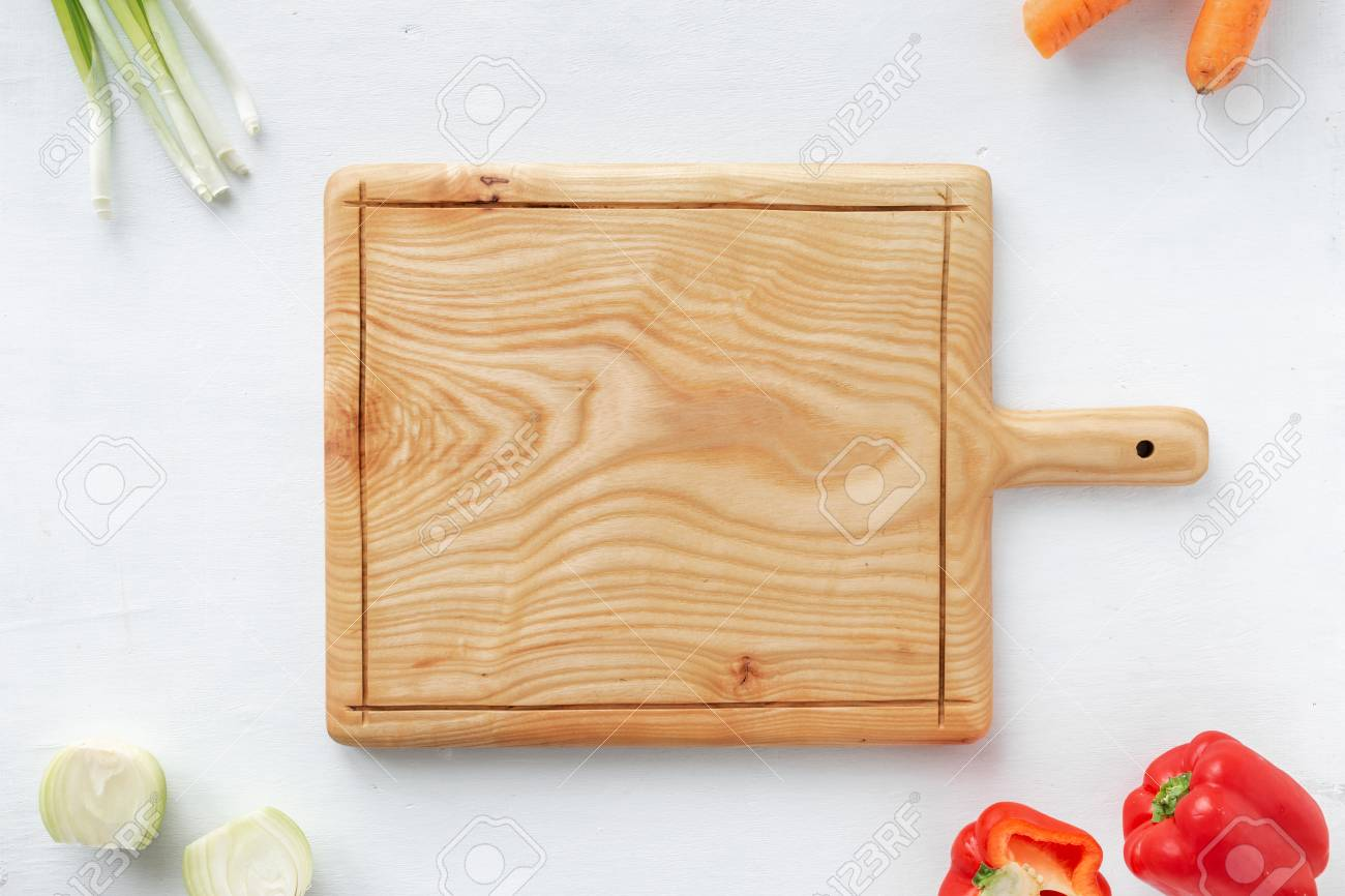 Cutting board handmade with vegetables on wooden kitchen table..