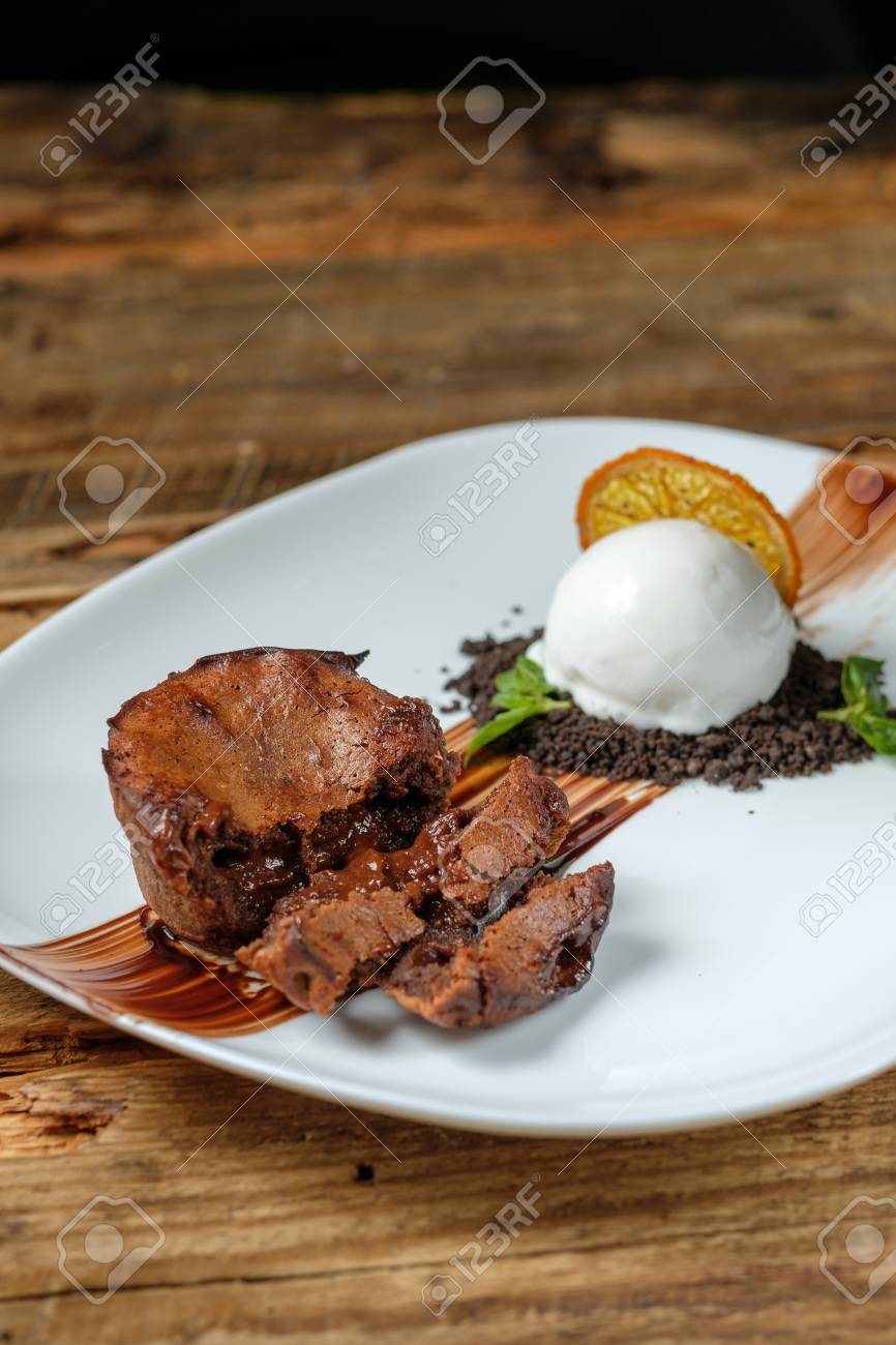 Warm dessert chocolate cake Fondant served on plate with scoop