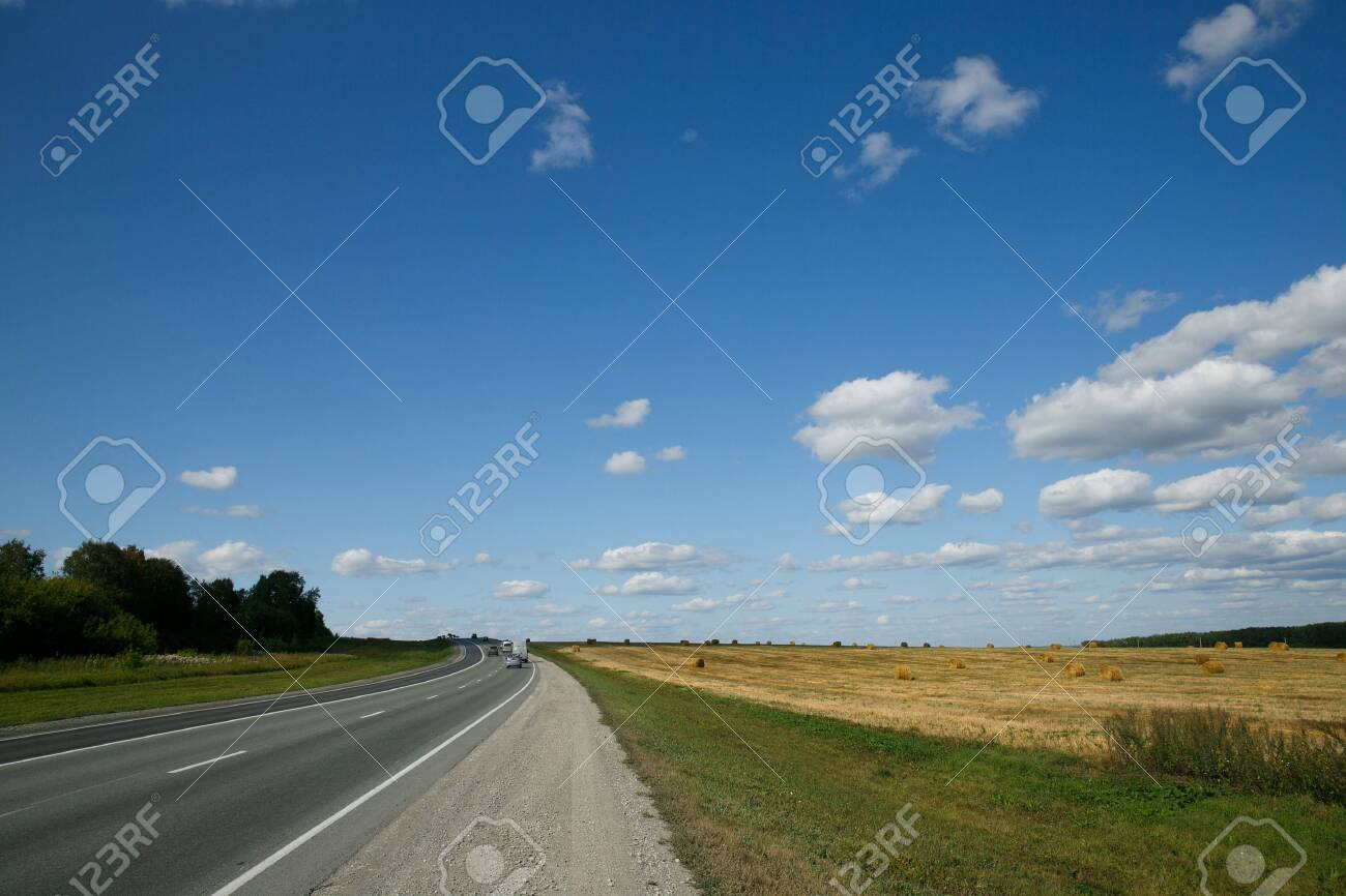 Intercity route passing fields and forests on a summer day with cloudy sky - 131885630