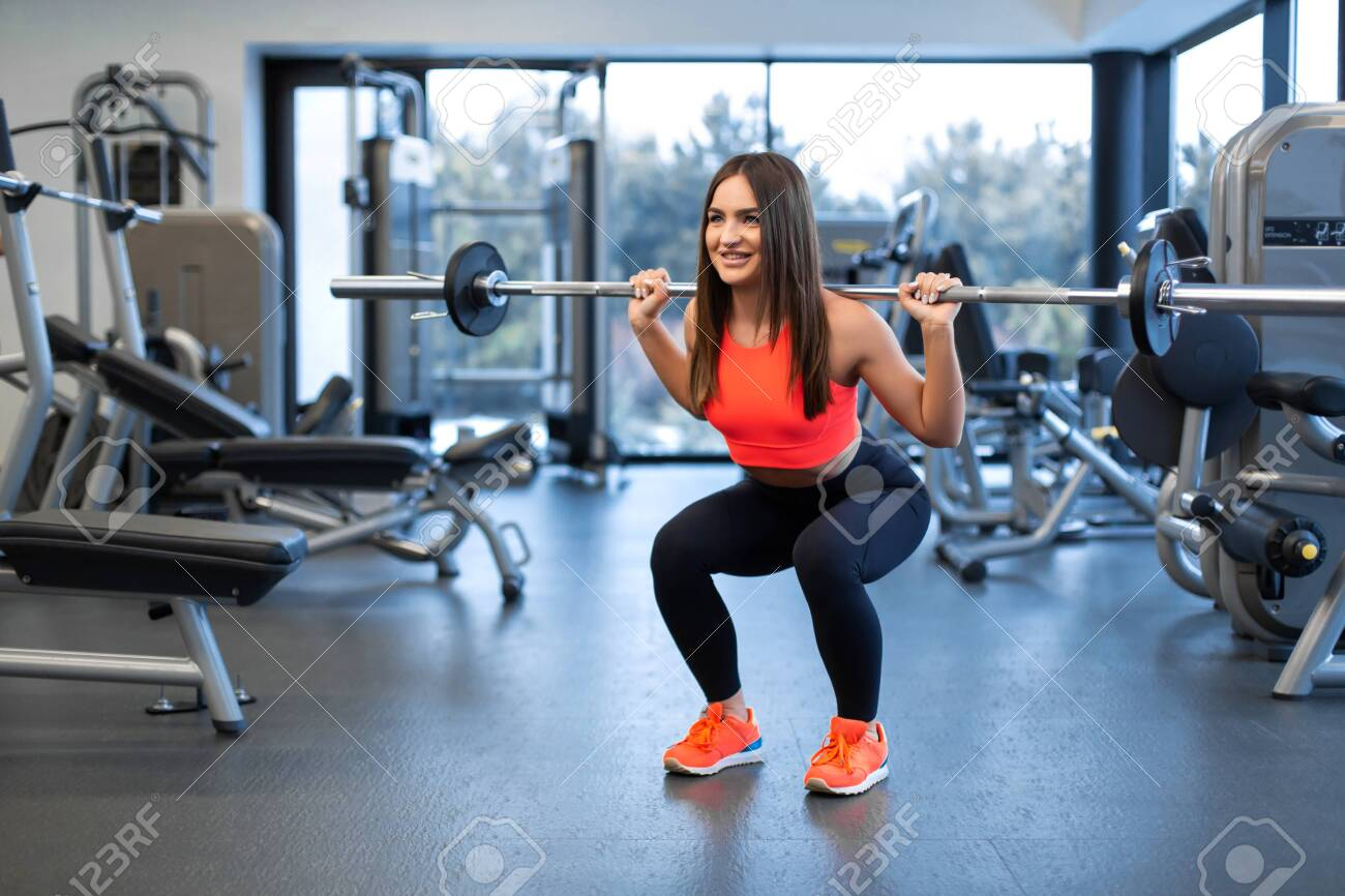 slim handsome young woman in sportswear squats with a barbell on the shoulder in the gym. - 120354726