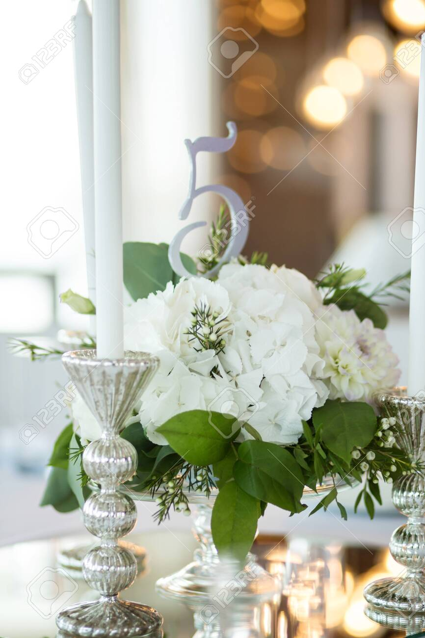Wedding table setting is decorated with fresh flowers and white candles. Wedding floristry. Bouquet with roses, hydrangea and eustoma. On the background blur are burning garlands with light bulbs. - 131185548