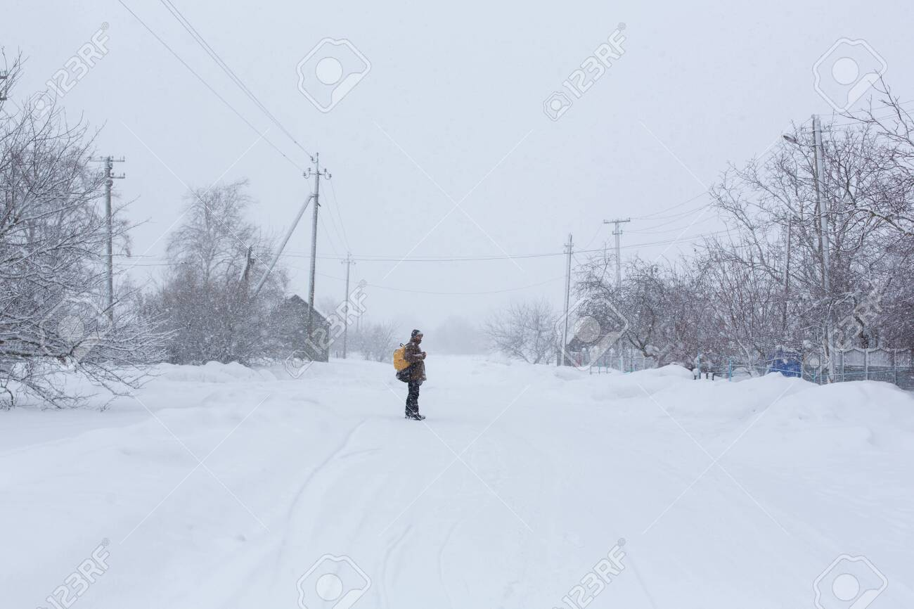 A rustic man is walking down the street in winter with a yellow backpack. Snow blizzard. - 136692525